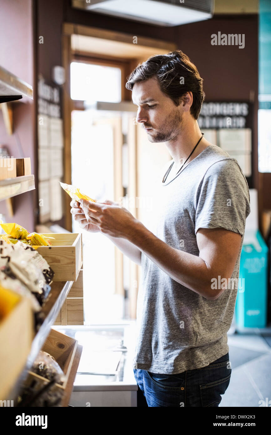 Young man reading label in grocery store - Stock Image