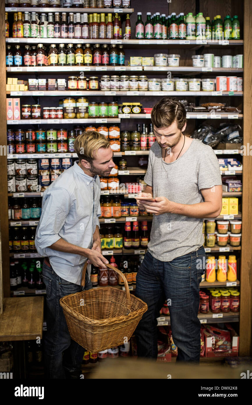 Young male friends reading label against shelf in supermarket - Stock Image