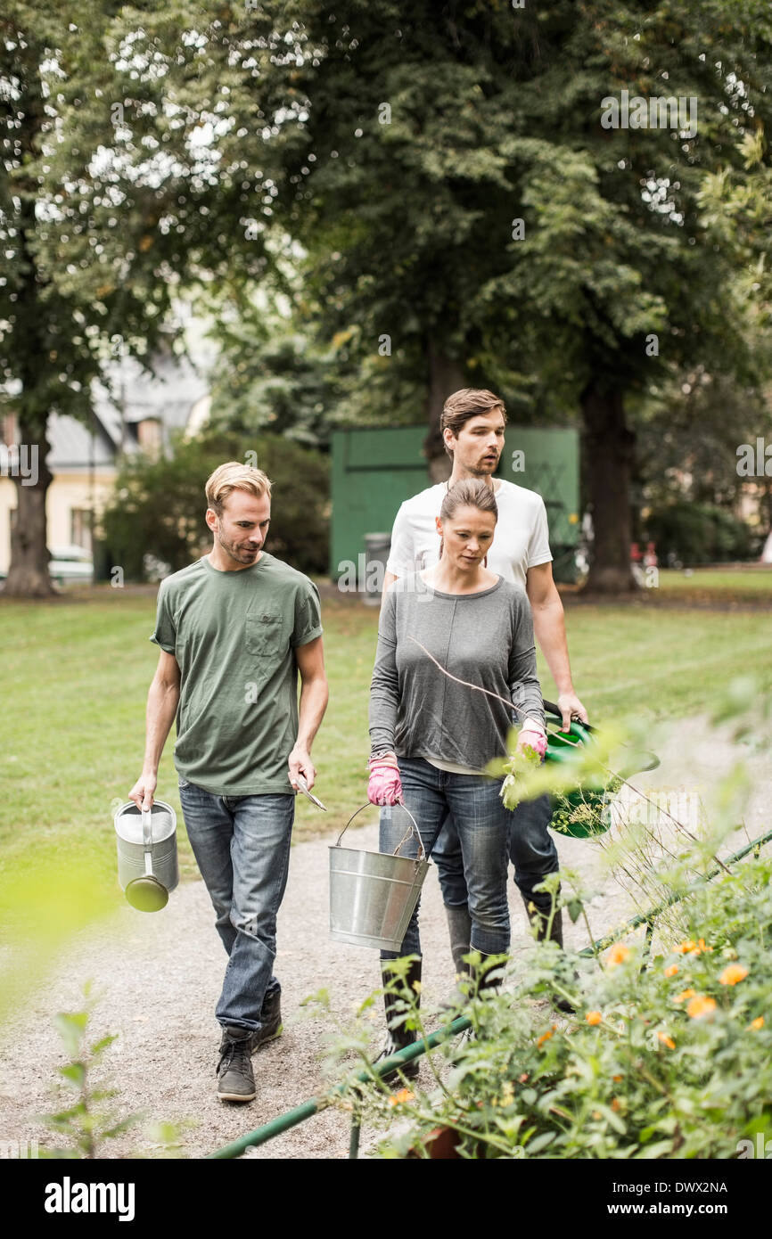 Friends with gardening equipment walking by garden - Stock Image