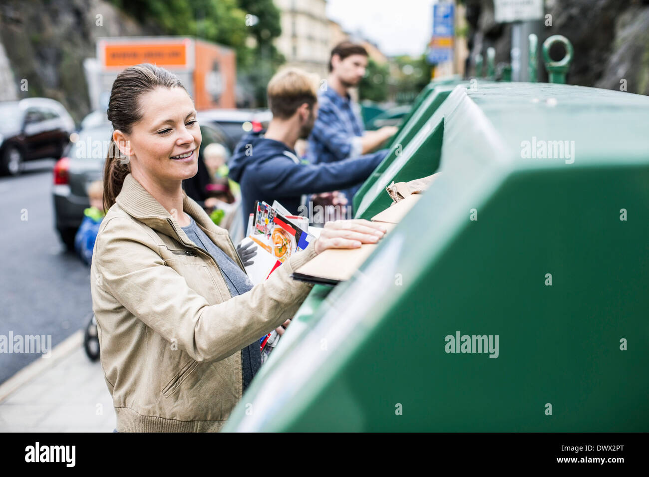 Woman and friends putting recyclable materials into recycling bins - Stock Image