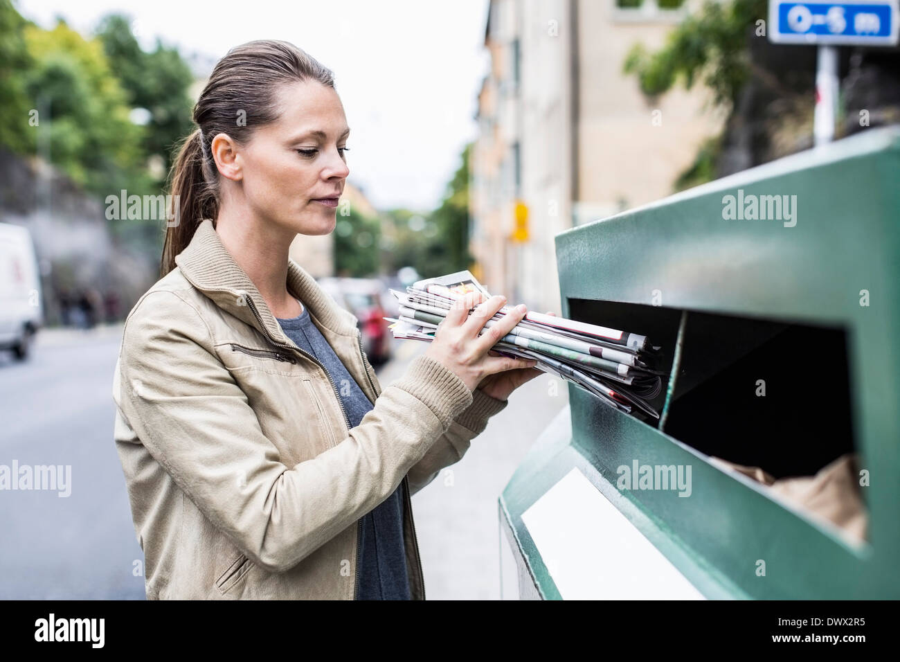 Mid adult woman putting newspapers into recycling bin - Stock Image