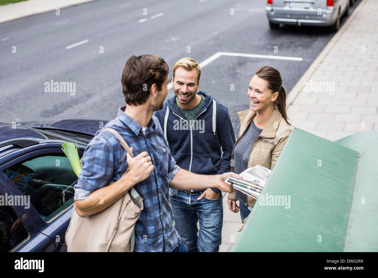 Happy friends with man putting  newspaper in recycling bin - Stock Image