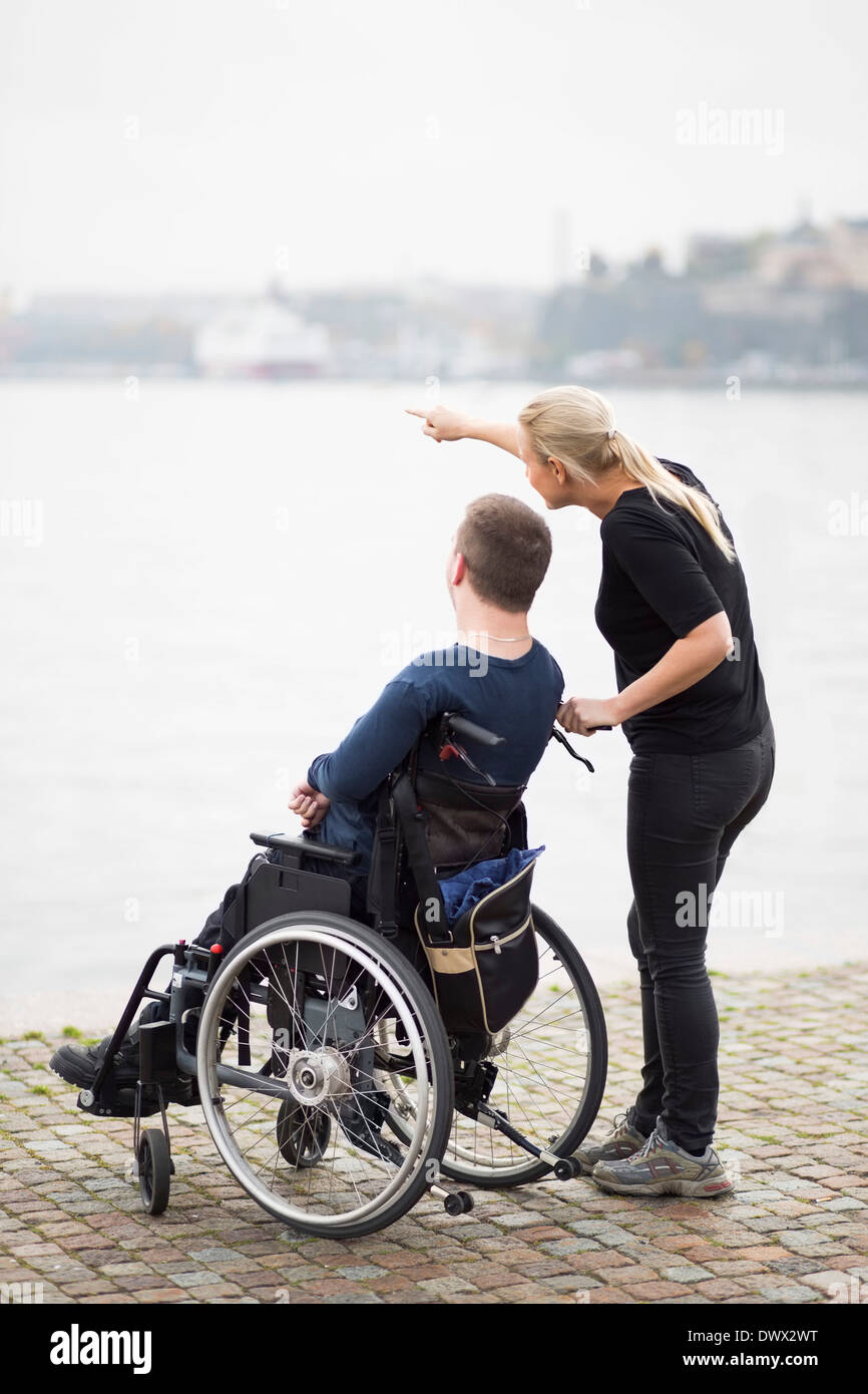 Caretaker showing something to disabled man on wheelchair by lake Stock Photo