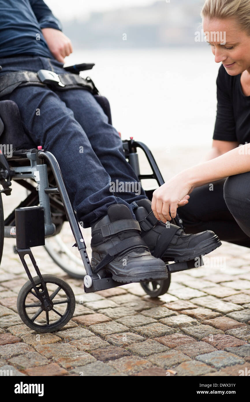Female caretaker putting on disabled man's shoes outdoors - Stock Image