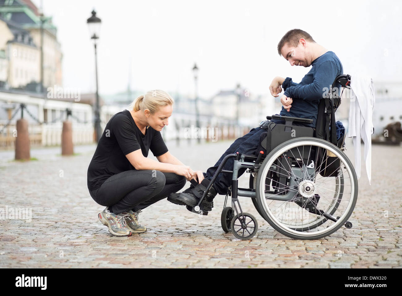 Female caretaker putting on disabled man's shoes on street - Stock Image