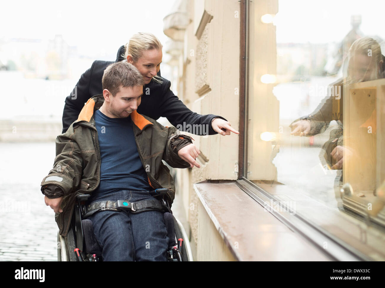Disabled man on wheelchair widow shopping with caretaker Stock Photo