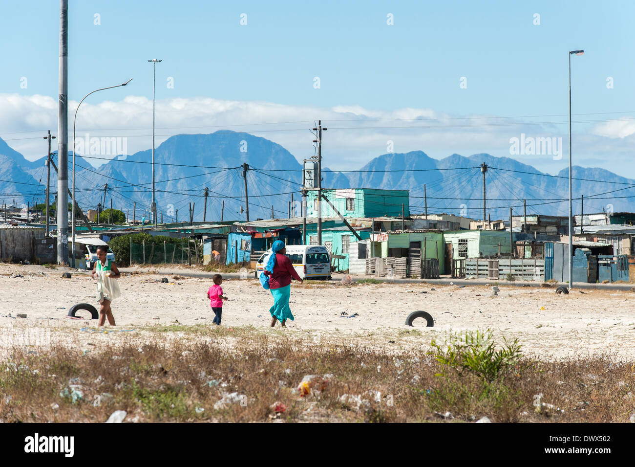 Woman with child crossing a sandy playground in Khayelitsha, Cape Town, Western Cape, South Africa - Stock Image