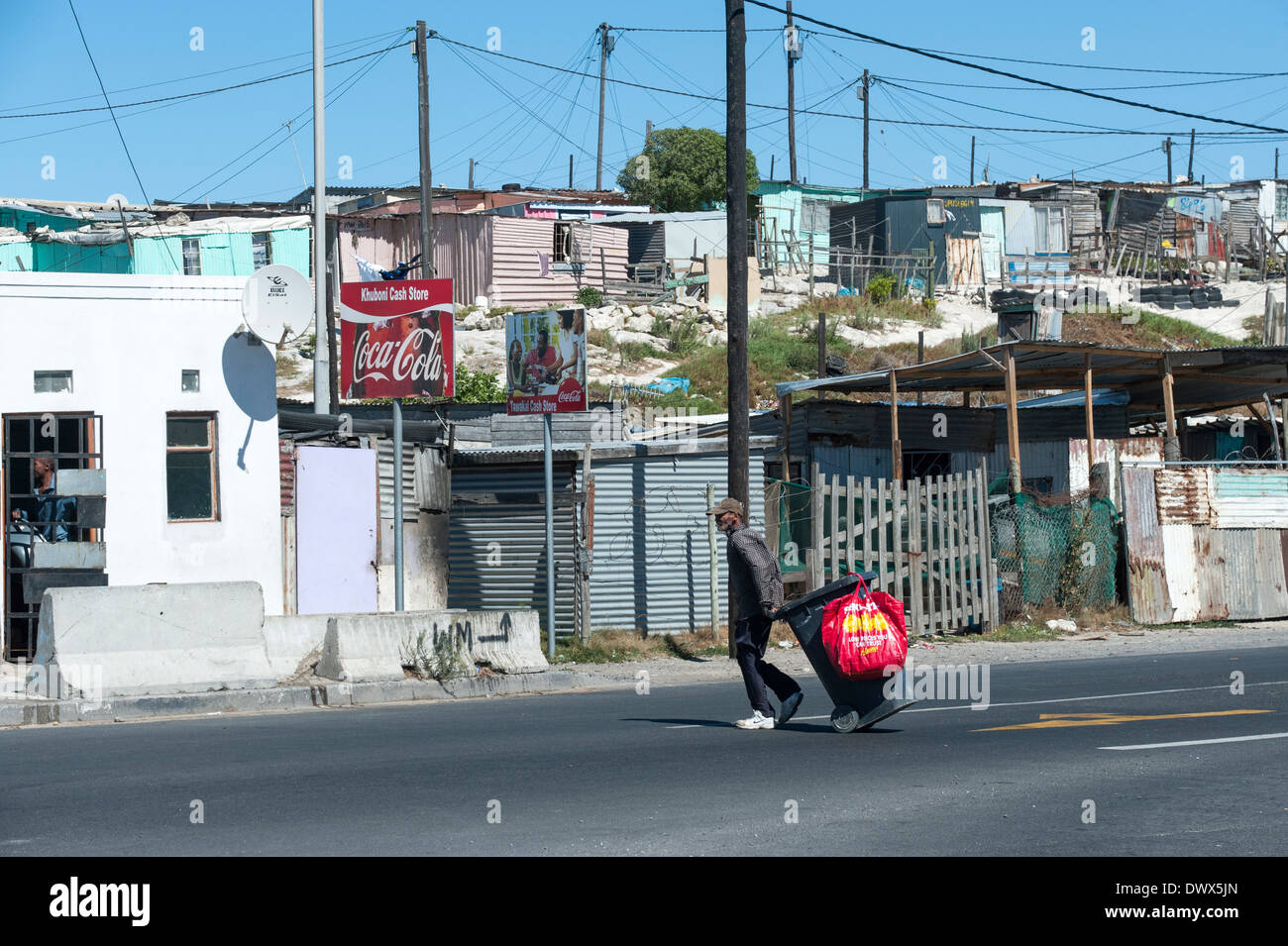 Man pulling a rubbish bin along a street in Khayelitsha, Cape Town, Western Cape, South Africa - Stock Image
