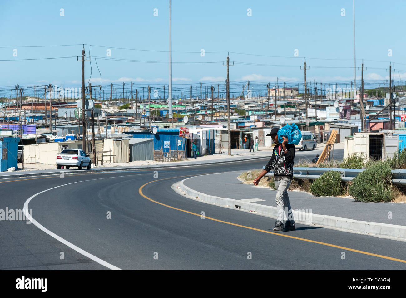Man carrying a bag crosses a road in Khayelitsha, Cape Town, Western Cape, South Africa - Stock Image