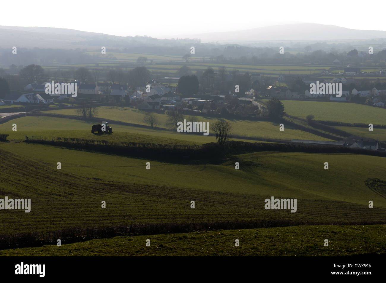 Spring and a farmer toils in field with tractor outside village in low misty  light - Stock Image