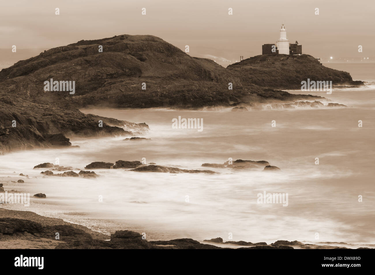 Mumbles Head and Lighthouse shrouded in spray sepia tone in Swansea Bay, site of proposed tidal Lagoon. The light Stock Photo