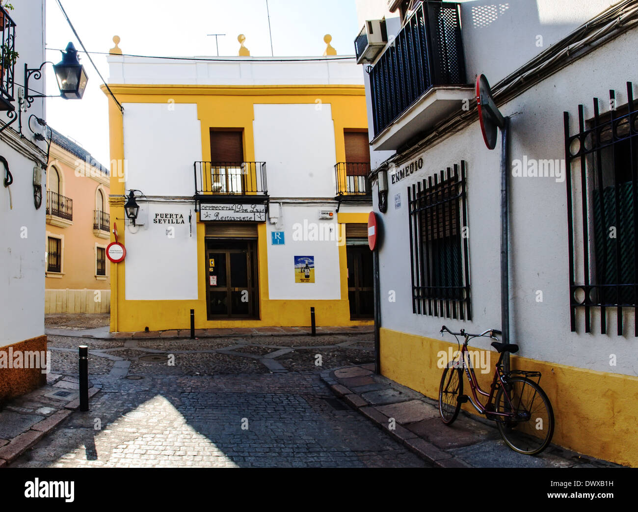 Deserted cobbled street in Spain with yellow and white buildings and bicycle - Stock Image