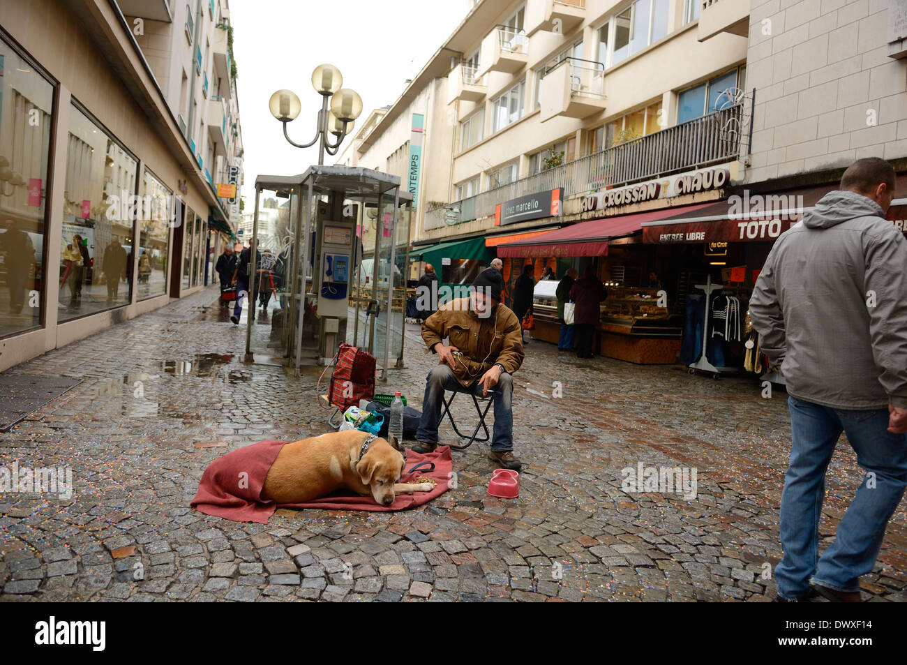 Homeless man with his dog on the streets of Rouen. Normandy. France - Stock Image