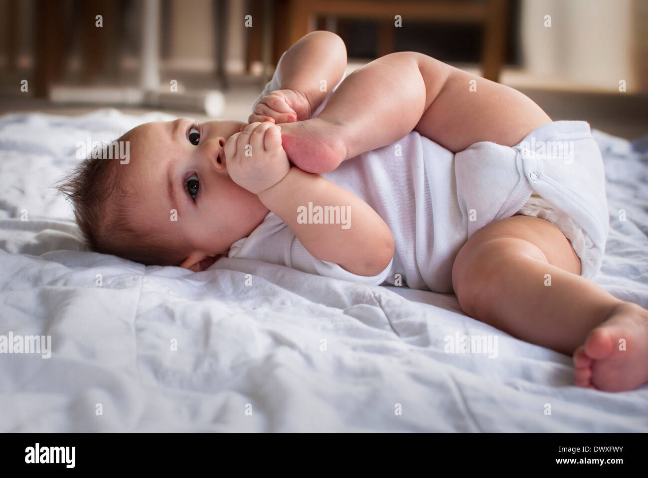Baby with her feet in her mouth - Stock Image