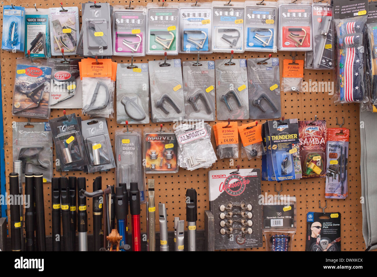 Shop display on pegboard of musical accessories including guitar capos, bottlenecks, whistles, machine heads, etc. - Stock Image