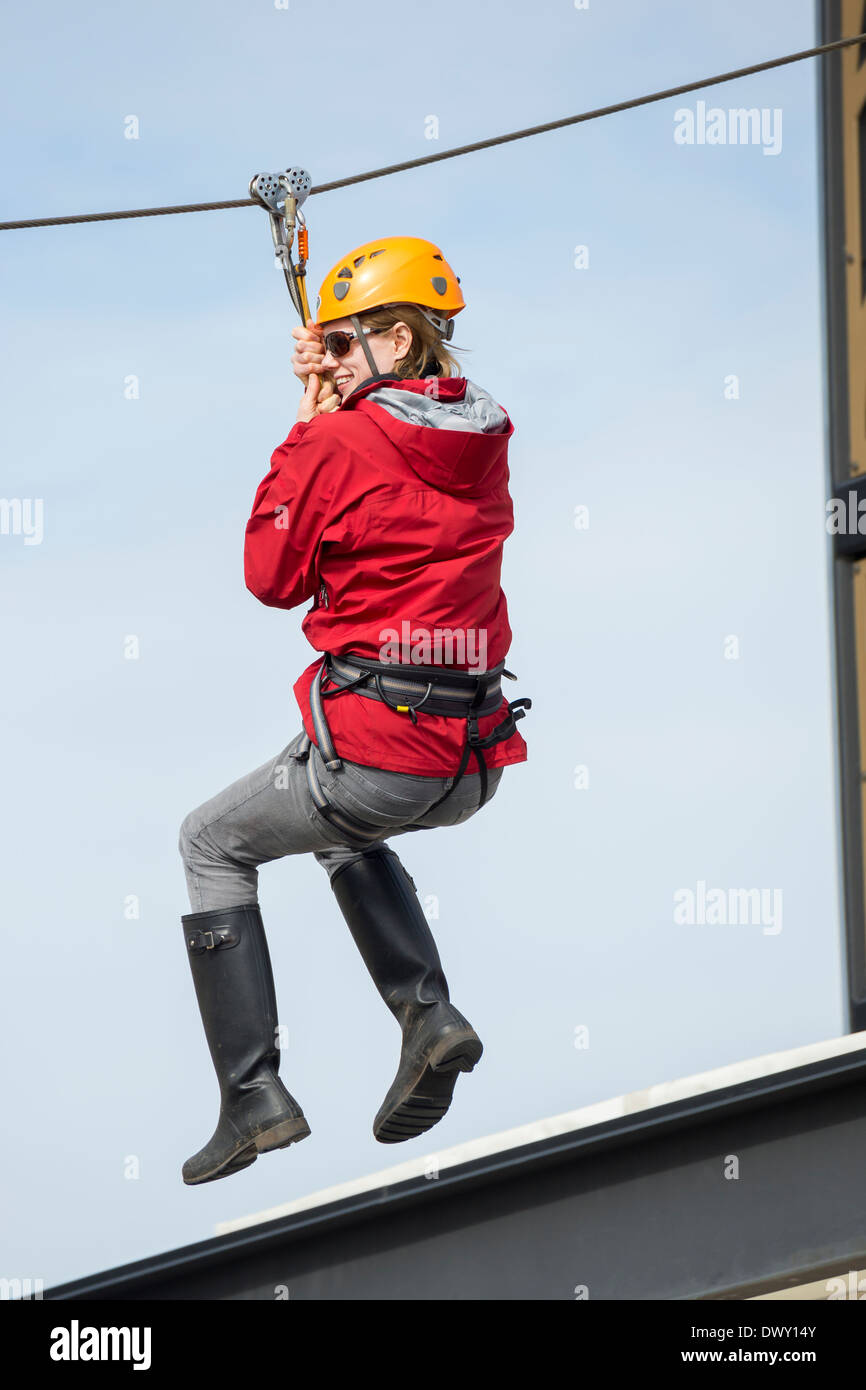 Female Zip Line rider zipping over Uptown Mall shopping center at Spring Break-Victoria, British Columbia, Canada. - Stock Image