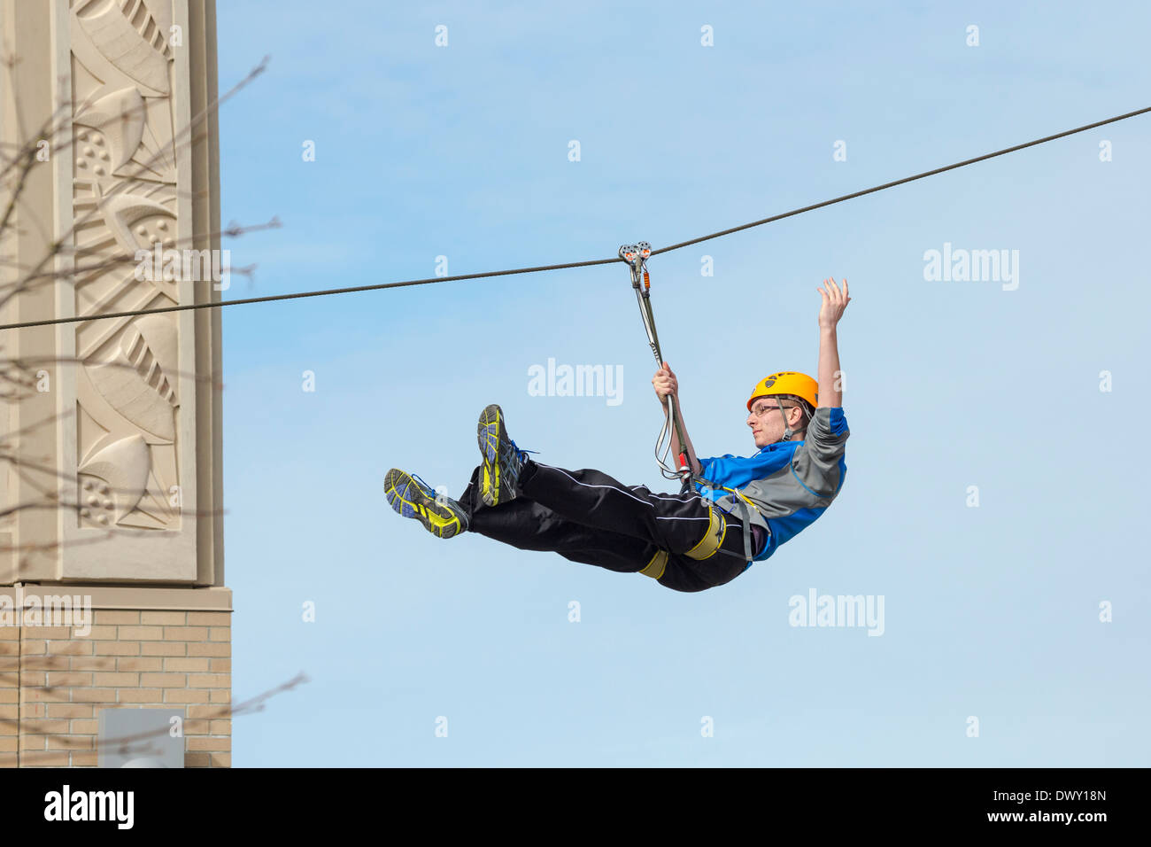 Young man Zip Line rider zipping over Uptown Mall shopping centre at Spring Break-Victoria, British Columbia, Canada. - Stock Image