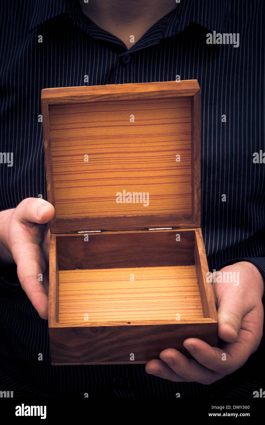An empty casket in the hands of a man - Stock Image