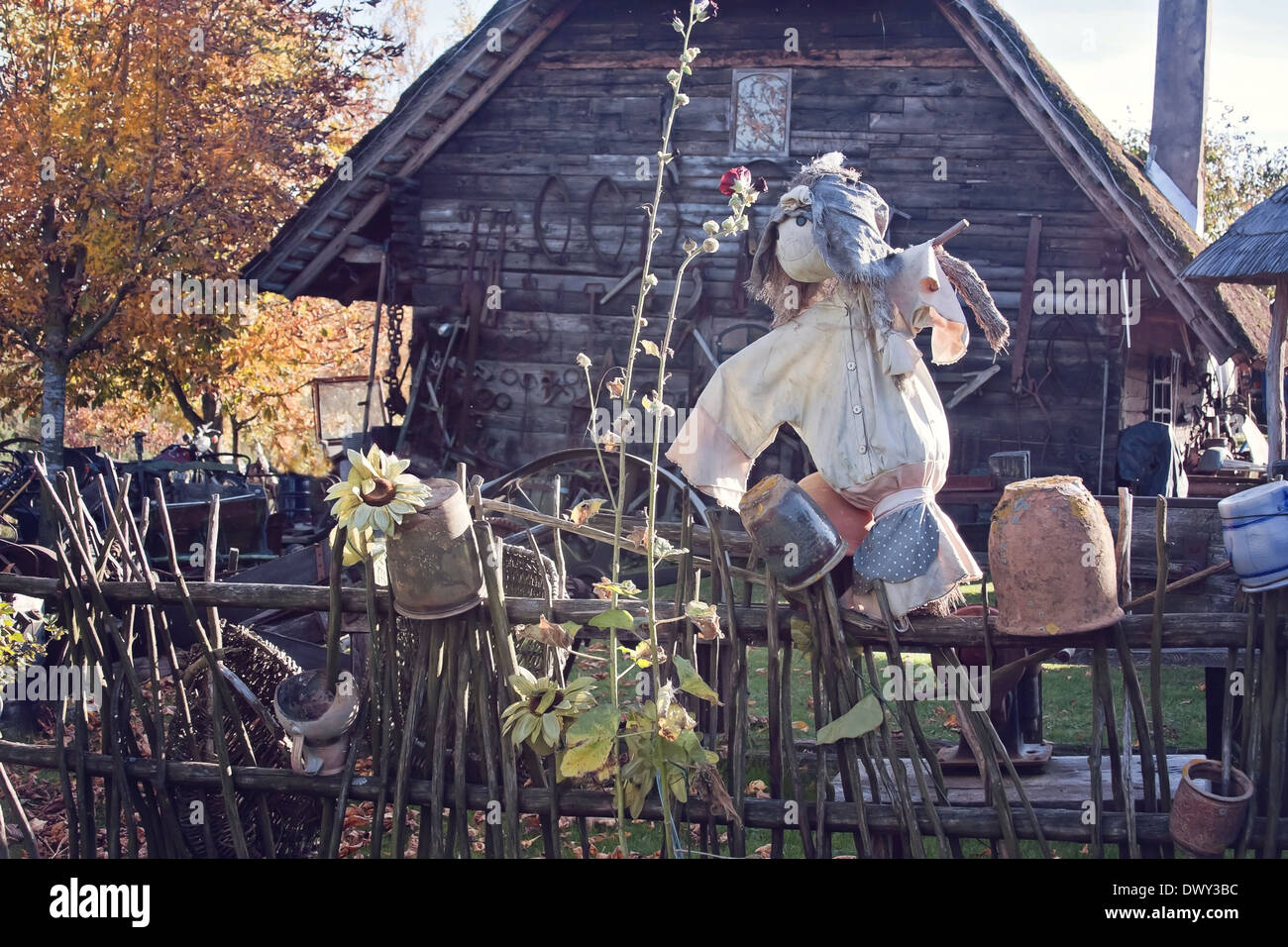 scarecrow on a fence, old wooden house in a background - Stock Image