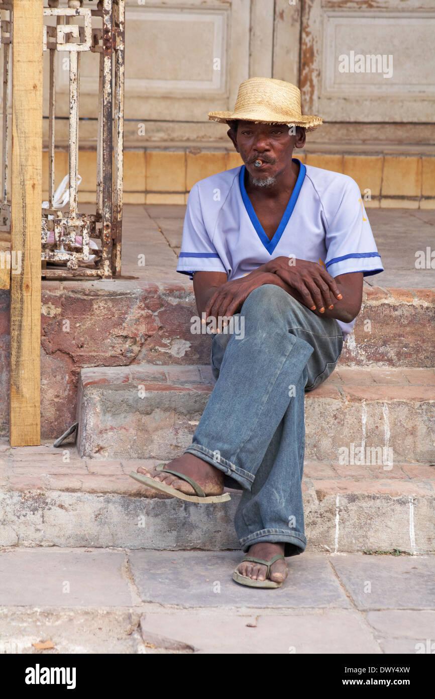 Daily life in Cuba - afro-caribbean man sat on steps smoking a cigar at Trinidad, Cuba - Stock Image