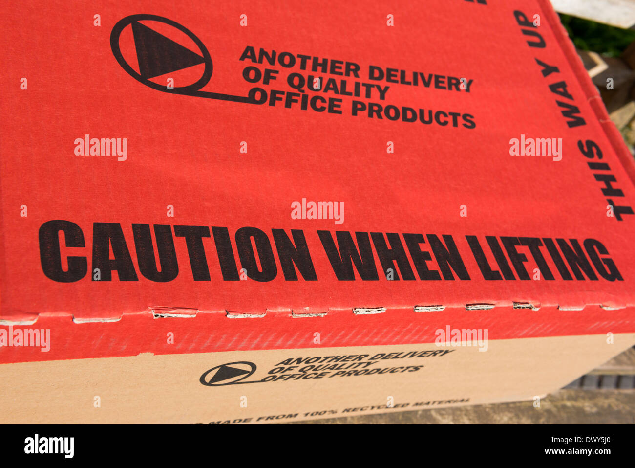 A cardboard delivery box with health and warning and safety information. - Stock Image