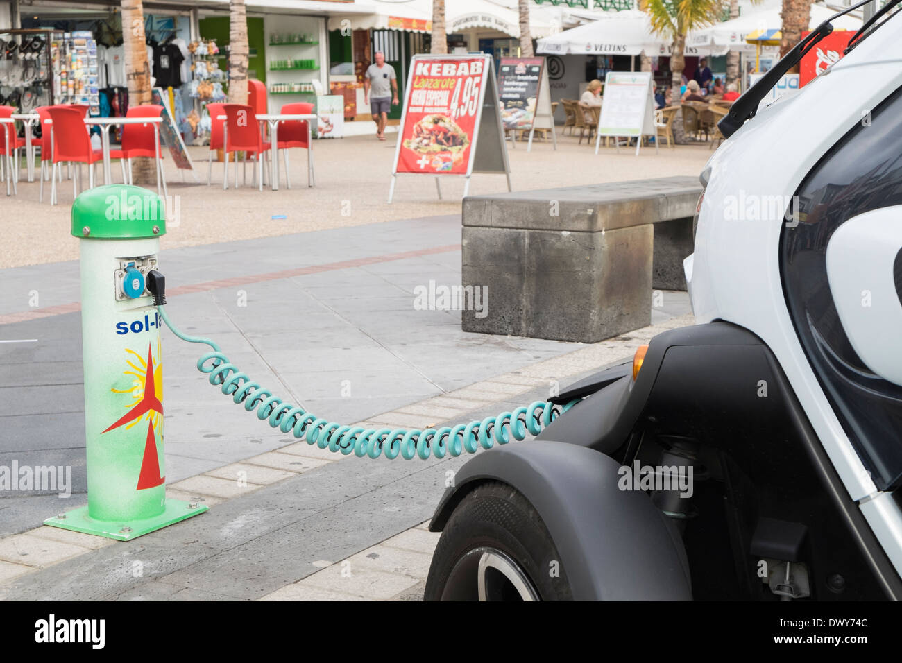 Renault Twizy battery-powered electric car plugged in to a Sol-lar battery charging point on roadside in Canary Islands Spain - Stock Image