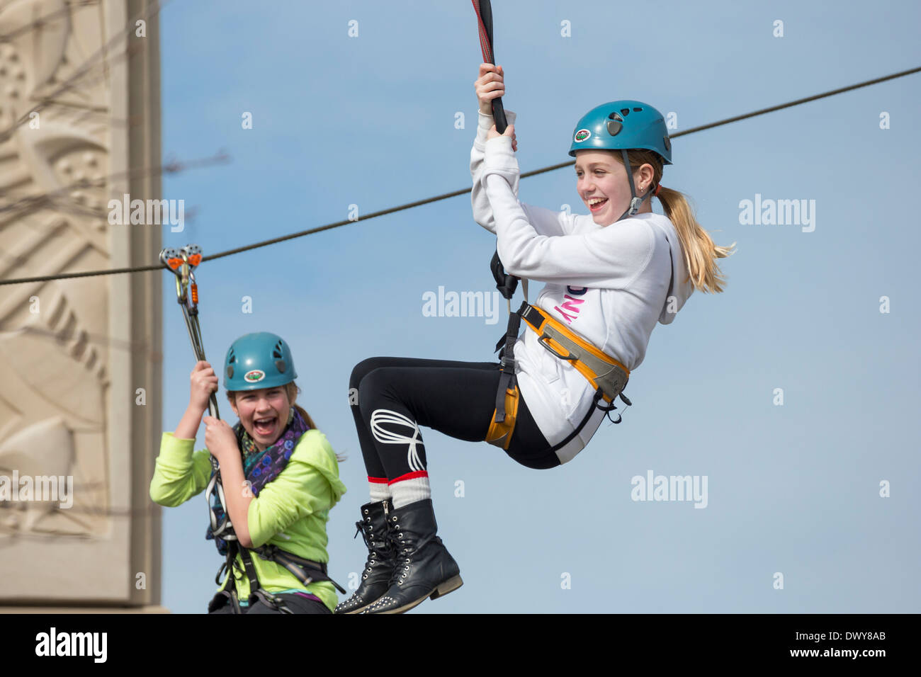 Two young girls on Zip line zipping over Uptown Mall shopping center at Spring Break-Victoria, British Columbia, Canada. - Stock Image
