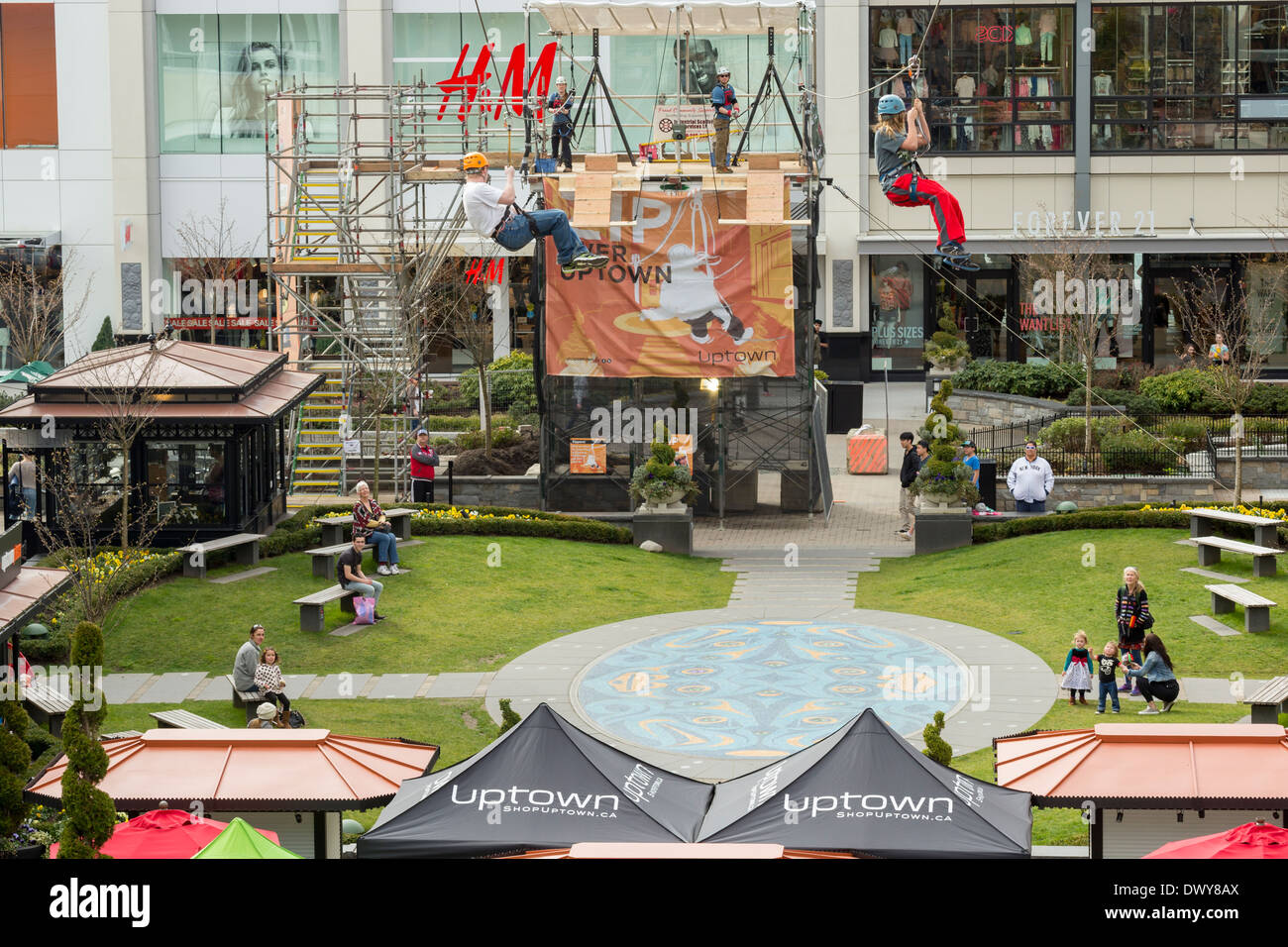 People zipping down Zip Line setup over Uptown Mall shopping center at Spring Break-Victoria, British Columbia, Canada. - Stock Image