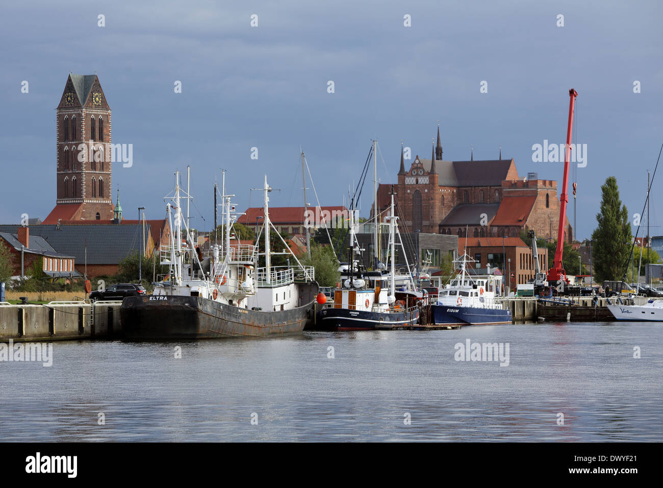 Wismar, Germany, Age fishing harbor with church St. Mary's and St. George's Church - Stock Image