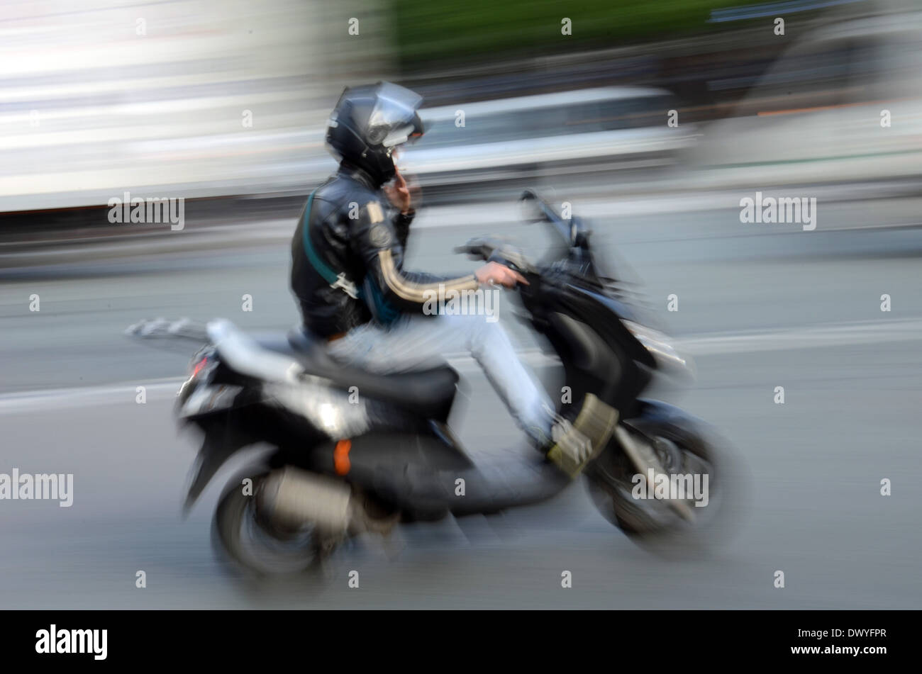 A scooter driver in the city. - Stock Image