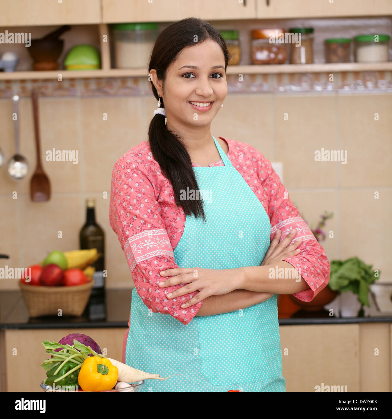 Smiling Young Indian Woman In Kitchen With Fresh Vegetablets And