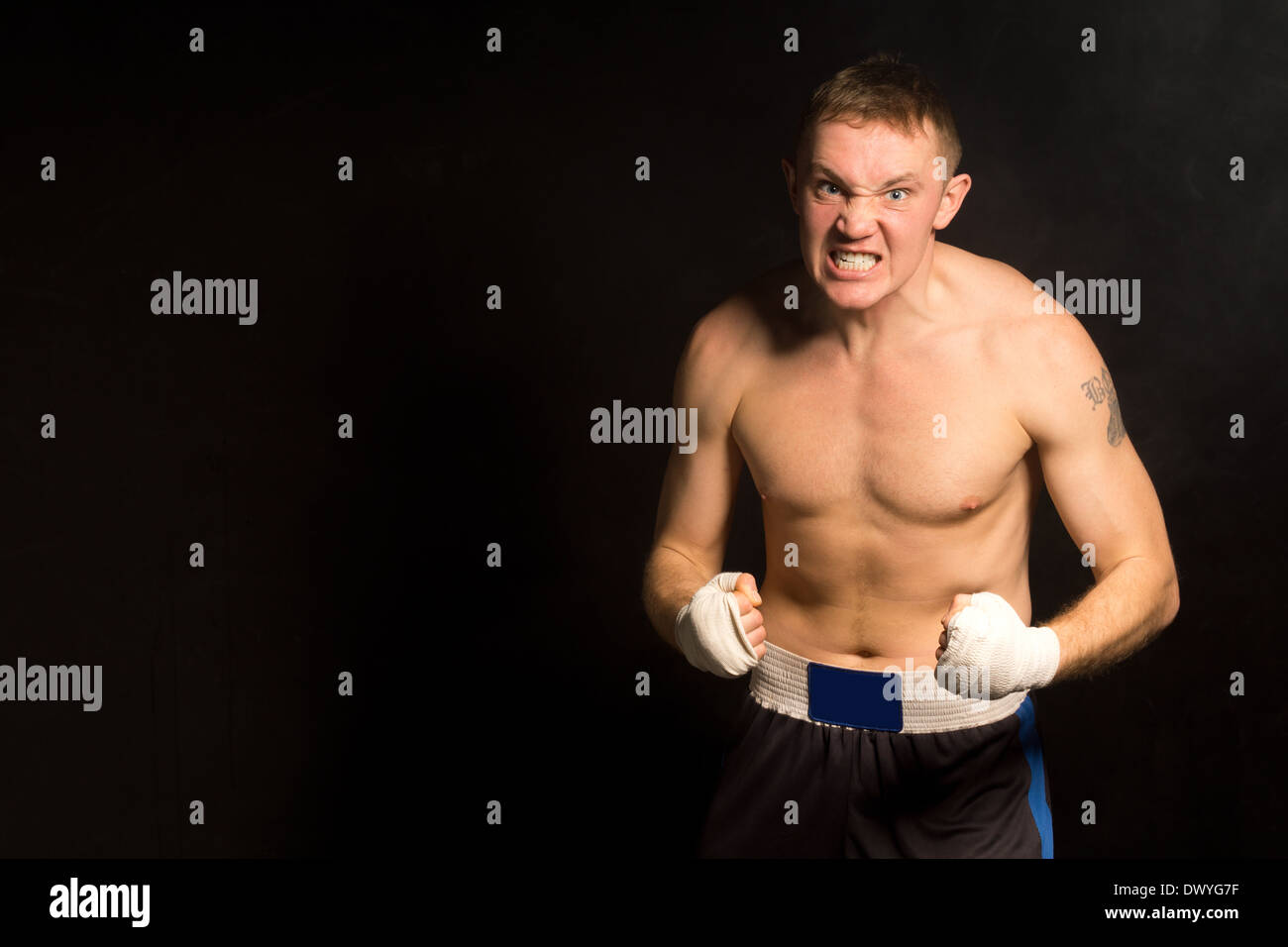 Angry determined young boxer gritting his teeth with clenched bandaged fists on a dark background with copyspace - Stock Image