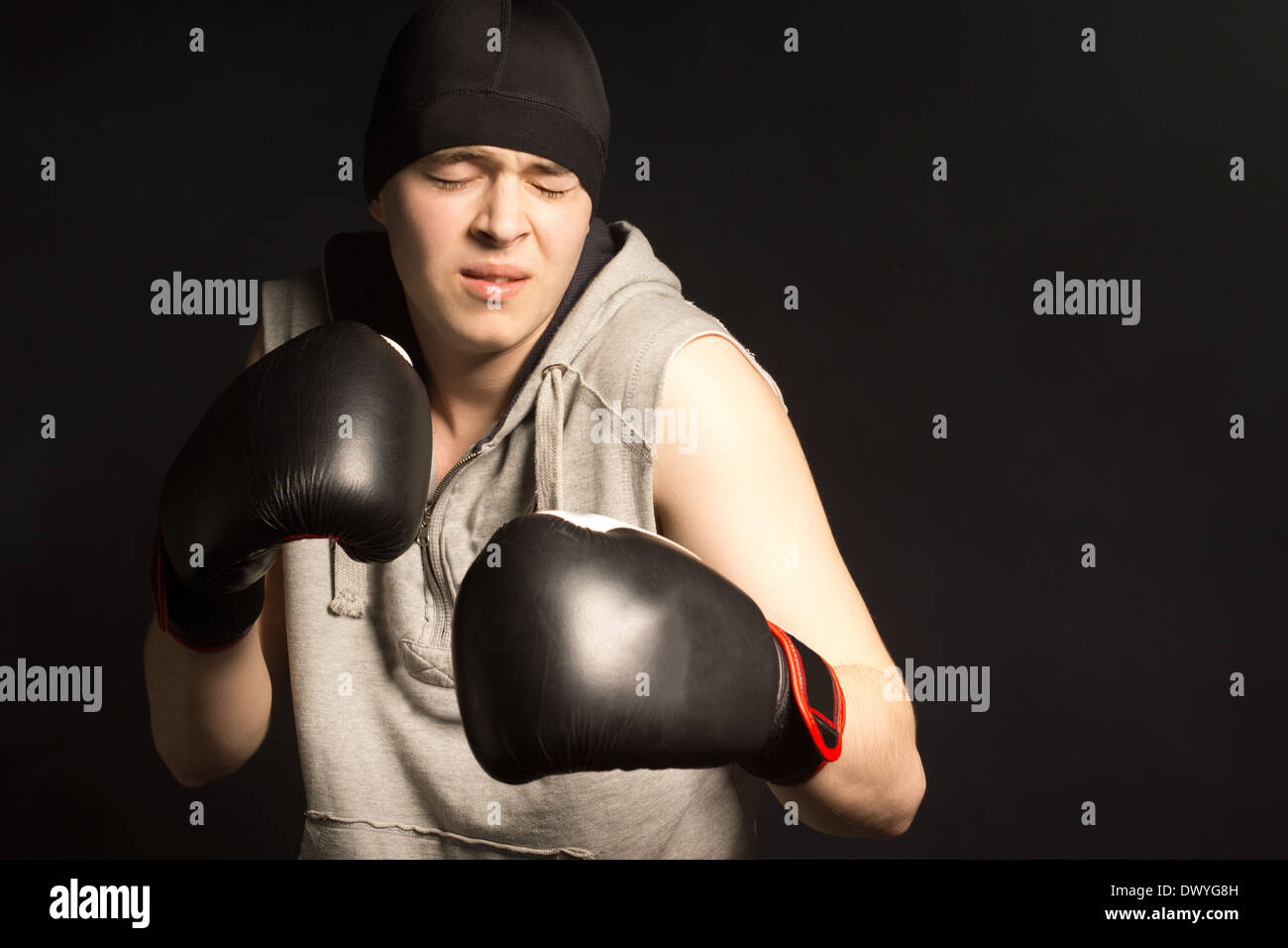 Young boxer grimacing in pain as he stands with his gloved fists raised in the darkness - Stock Image