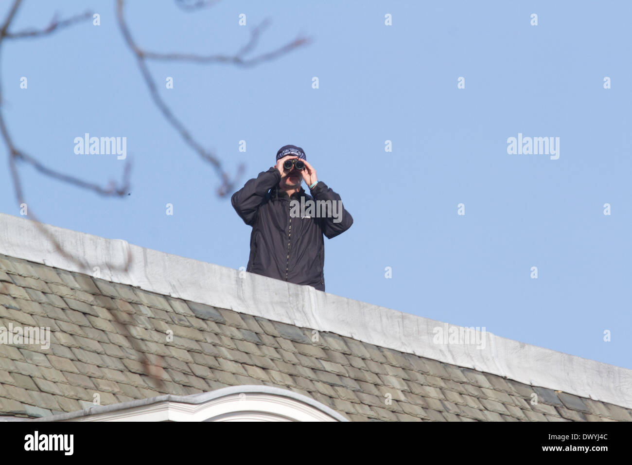 London UK. 14th March 2014. A policeman with binoculars on the rooftop of the American Ambassador residence in London as  US Secretary of State John Kerry was meeting his Russian counterpart foreign minister Sergei Lavrov in London to discuss the Ukranian crisis and the referendum in Crimea - Stock Image
