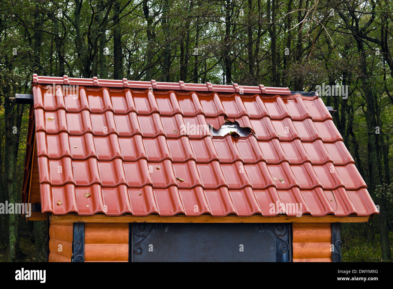 Barbarism: a hole in the new roof of the small house - Stock Image