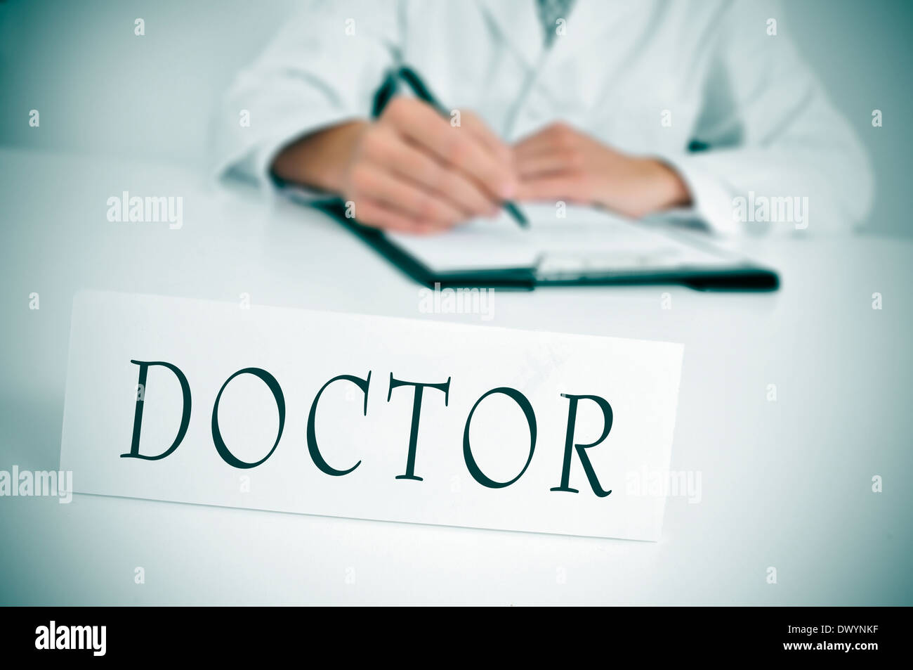 a doctor sitting in the desk of his consulting room writing in a clipboard and a nameplate with the word doctor written in it - Stock Image