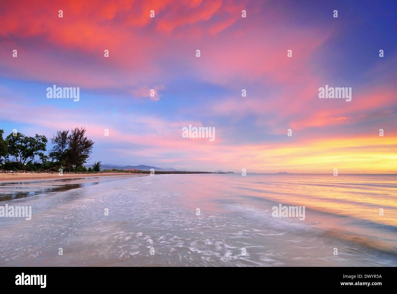 Tropical sunset and waves at the beach in Kota Kinabalu, Sabah, Borneo, Malaysia. - Stock Image