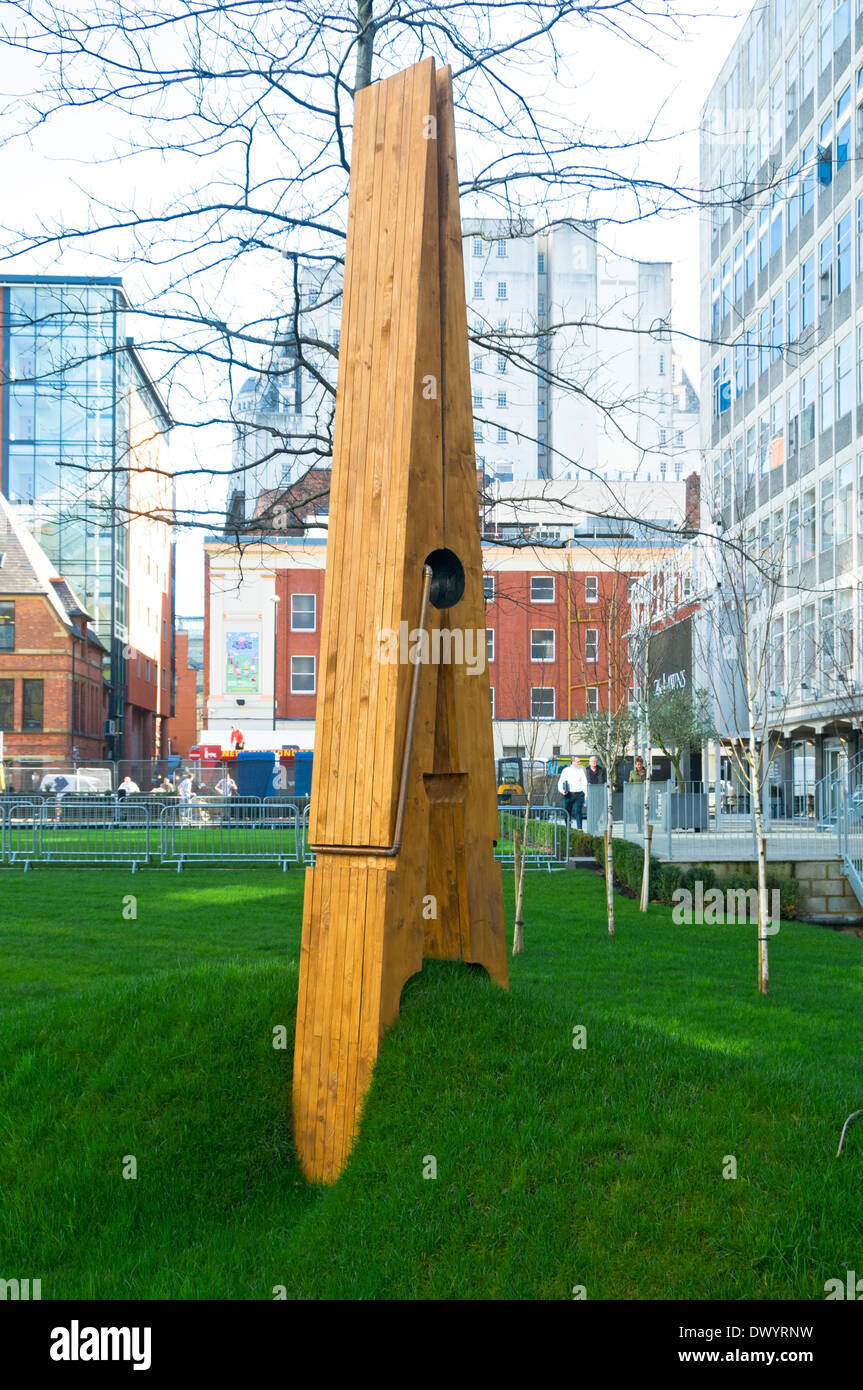 Sculpture of an old fashioned wooden clothes peg 'pinching' the lawn. The Lawns, Spinningfields, Manchester, England, UK - Stock Image