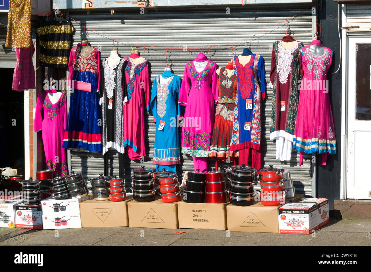 Brightly coloured dresses and cooking pans outside an Asian shop, Oldham, Greater Manchester, England, UK - Stock Image