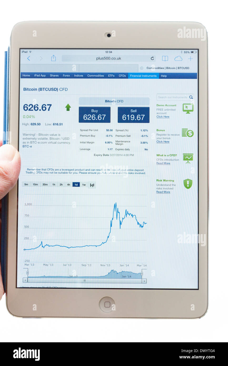 Person holding an iPad tablet whilst looking at Plus500 trading website quoting cryptocurrency Bitcoin exchange rate prices in USD money for cryptos - Stock Image