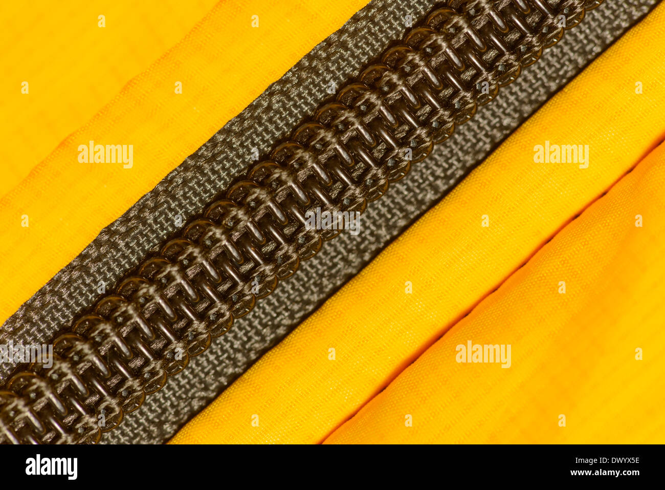 A coil zipper made of spiral plastic elements sewn into a yellow waterproof coat. - Stock Image