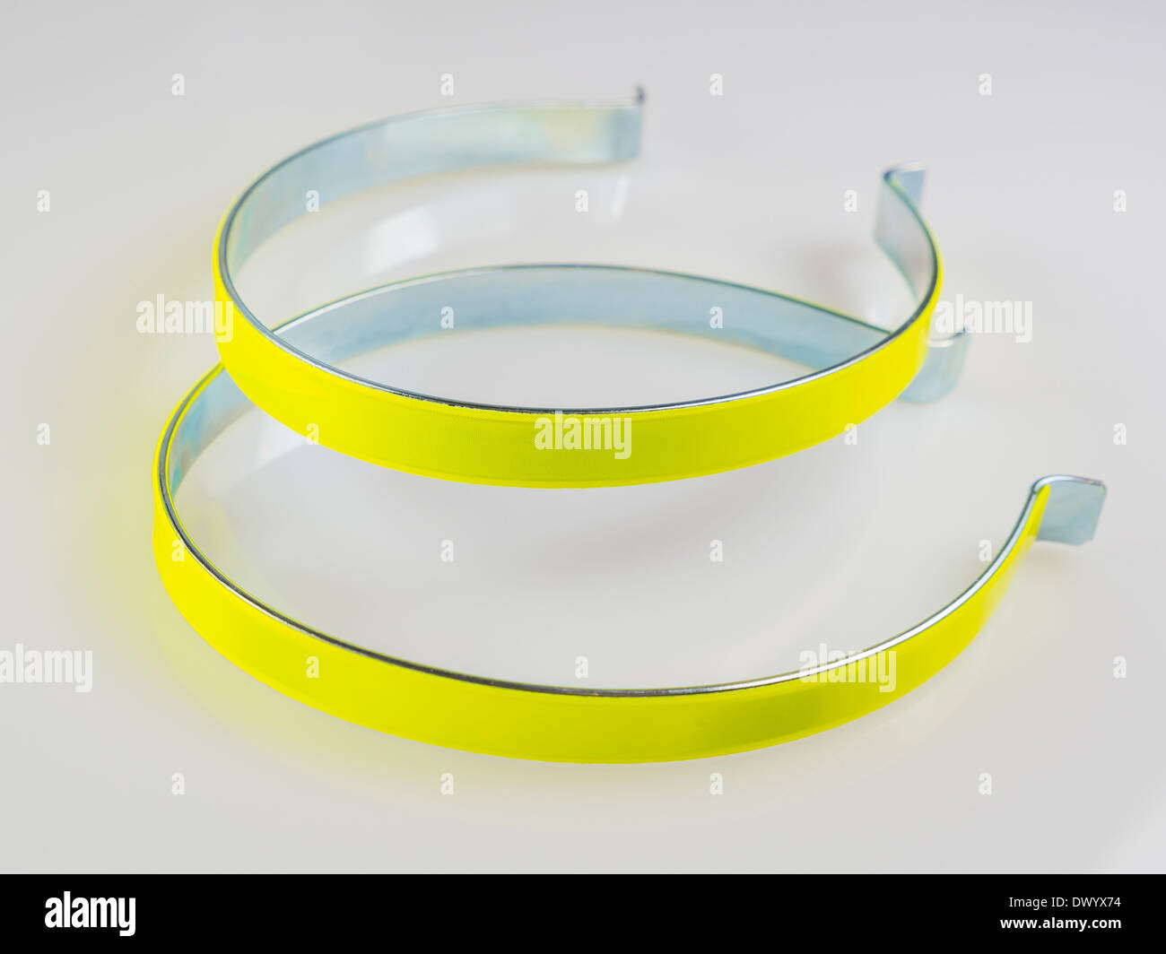Luminous and reflective yellow bicycle clips for night time safety. - Stock Image