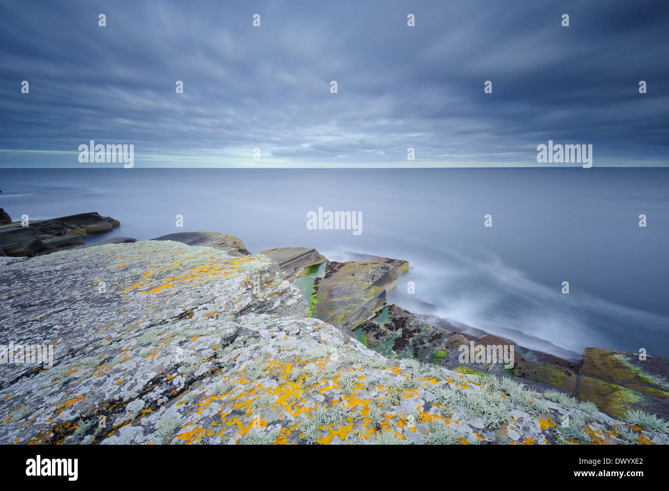 Long exposure picture of sandstone rocks and the sea on the coast at Wick, Caithness, north Scotland. - Stock Image