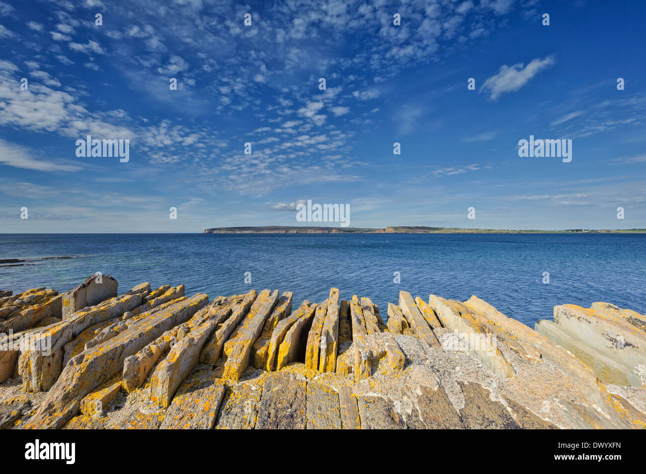 The harbour wall at Castletown made from flagstones, looking across to Dunnet Head, Caithness, Scotland. - Stock Image