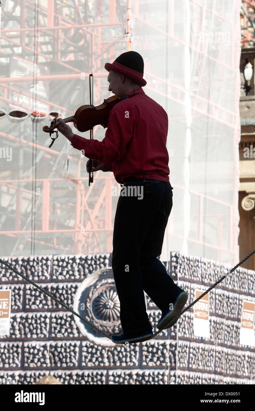 Busker on tightrope playing violin, Bath, Somerset, England, UK - Stock Image