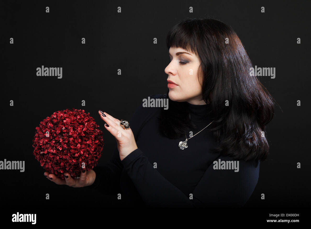 medium woman or fortune teller holds red magic ball - Stock Image