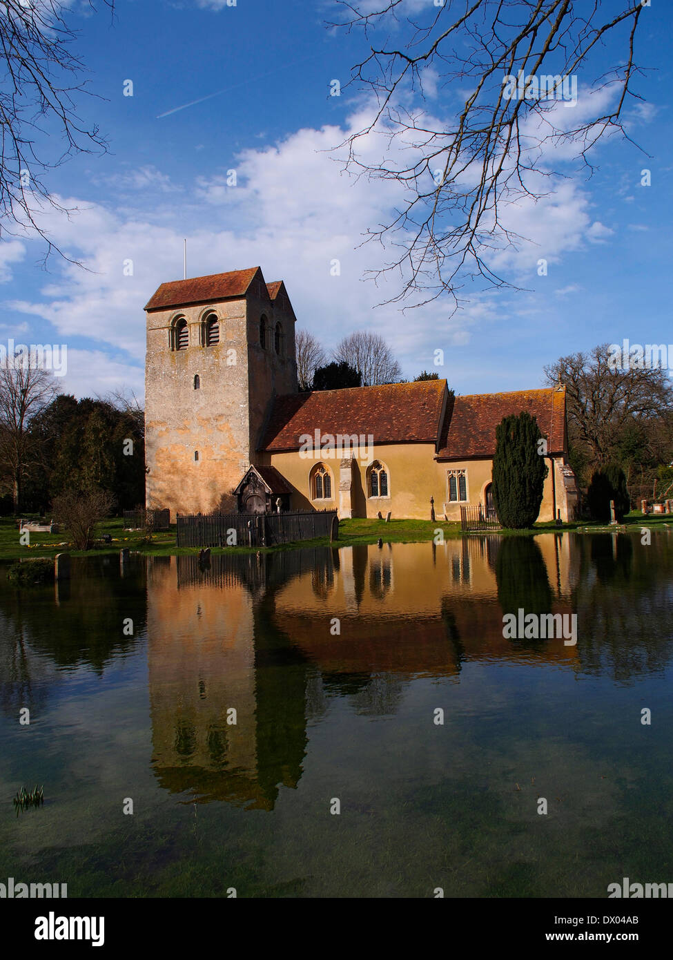 First signs of Spring but the St Bartholomew church in Fingest, Buckinghamshire is still surrounded by flood water - Stock Image