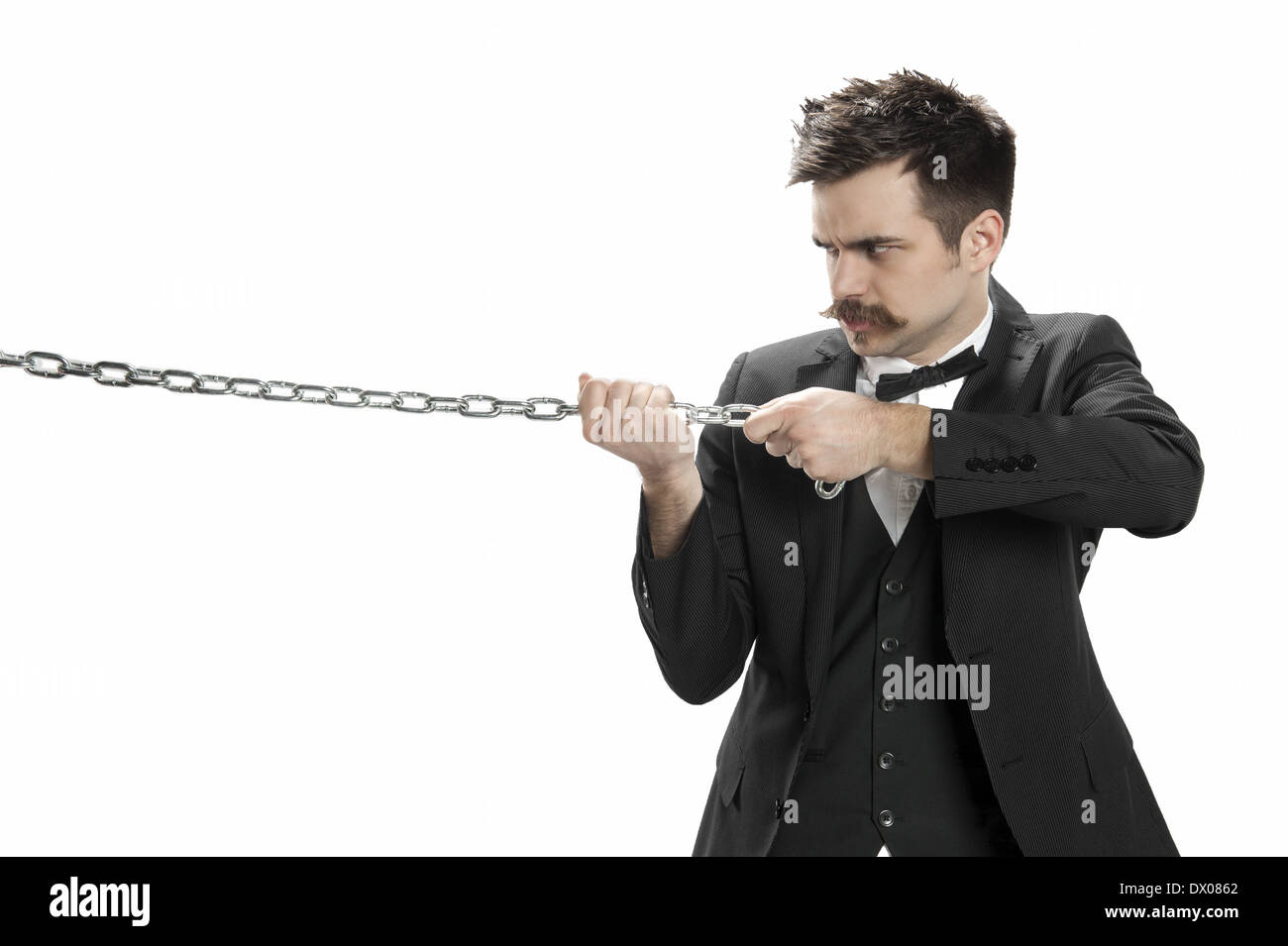 Young man in business suit and bowtie scowls and pulls on a strtong chain - Stock Image