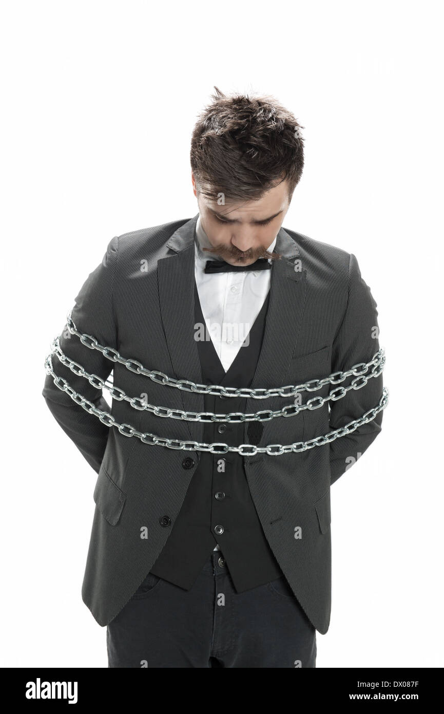 Attractive young man in business suit looks sullen as he stands with chains around him, isolated on white - Stock Image