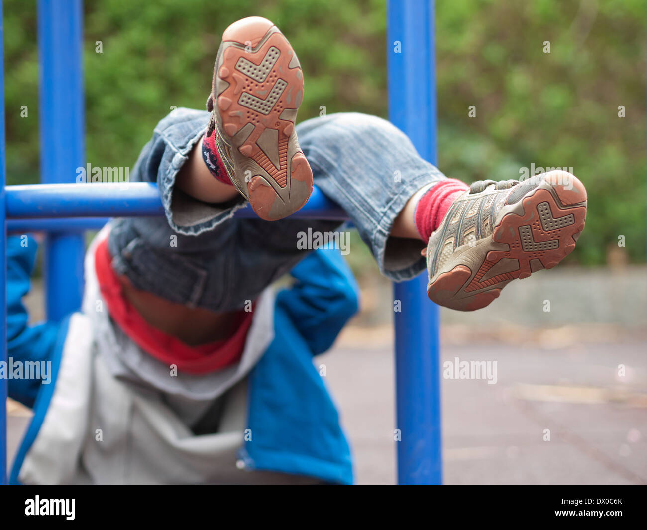 Child hanging upside down in climbing frame of a playground. Focus on feet with shoes only. Parts of climbing frame visible. - Stock Image